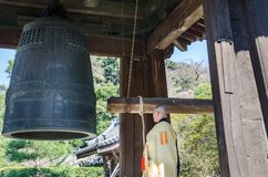 Monk and ancient temple bell in the Zen Buddhist Temple at Kamakura, Japan. KAMAKURA, JAPAN - MARCH 23,2014: Monk and ancient temple bell in the Zen Buddhist stock image