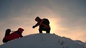 Εργασία και νίκη ομάδας Οι τουρίστες επεκτείνουν το χέρι στο φίλο που ανέρχεται στην κορυφή του λόφου Ορειβάτες το χειμώνα στο χι στοκ εικόνα