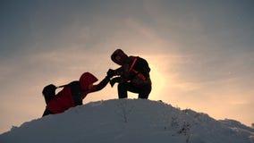 Εργασία και νίκη ομάδας Οι τουρίστες επεκτείνουν το χέρι στο φίλο που ανέρχεται στην κορυφή του λόφου Ορειβάτες το χειμώνα στο χι στοκ φωτογραφίες με δικαίωμα ελεύθερης χρήσης
