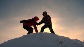Εργασία και νίκη ομάδας Οι τουρίστες επεκτείνουν το χέρι στο φίλο που ανέρχεται στην κορυφή του λόφου Ορειβάτες το χειμώνα στο χι στοκ φωτογραφία με δικαίωμα ελεύθερης χρήσης