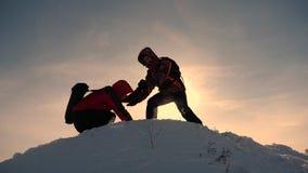 Εργασία και νίκη ομάδας Οι τουρίστες επεκτείνουν το χέρι στο φίλο που ανέρχεται στην κορυφή του λόφου Ορειβάτες το χειμώνα στο χι στοκ εικόνες