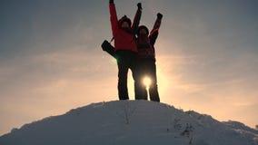 Εργασία και νίκη ομάδας Οι τουρίστες επεκτείνουν το χέρι στο φίλο που ανέρχεται στην κορυφή του λόφου Ορειβάτες το χειμώνα στο χι στοκ φωτογραφία