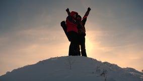Εργασία και νίκη ομάδας Οι τουρίστες επεκτείνουν το χέρι στο φίλο που ανέρχεται στην κορυφή του λόφου Ορειβάτες το χειμώνα στο χι στοκ φωτογραφίες