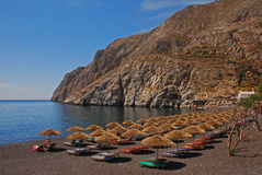 Kamari Town with her Popular Black Pebble Beach. Full with Huts for Sunbathing Royalty Free Stock Images