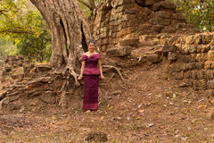 Kambodżańska dziewczyna w Khmer sukni Antycznym drzewem w Angkor Thom i ścianą, Angkor miasto Fotografia Stock