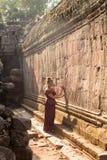 Kambodżańska dziewczyna w Khmer sukni przy Antycznym budynkiem Angkor miasto Zdjęcia Stock