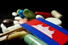 Kambodjansk flagga med lotten av medicinska preventivpillerar som isoleras på svart bakgrund Arkivbilder