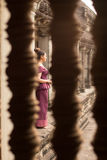 Kambodjansk flicka i en khmerklänning till och med ett fönster på Angkor Wat Arkivbild