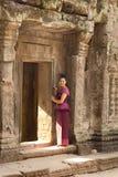 Kambodjansk flicka i en khmerklänning vid dörröppningen av forntida byggnad av den Angkor staden Arkivfoton