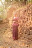 Kambodjansk flicka i en khmerklänning vid en forntida vägg i Angkor Thom, Angkor stad Royaltyfri Foto