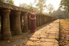 Kambodjansk flicka i en khmerklänning vid gångbanan till Phimeanakas i den Angkor staden Royaltyfri Foto