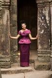 Kambodjansk flicka i en khmerklänninganseende i den Bayon templet i den Angkor staden Royaltyfri Foto