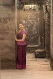 Kambodjansk flicka i en khmerklänninganseende i den Bayon templet i den Angkor staden Fotografering för Bildbyråer