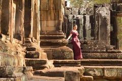 Kambodjansk flicka i en khmerklänninganseende på terrassen av elefanterna i den Angkor staden Royaltyfria Bilder