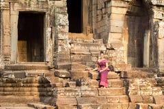 Kambodjansk flicka i en khmerklänningsammanträde på den Bayon templet i den Angkor staden Arkivfoto