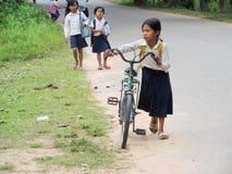 Kambodjansk flicka med bycicle som går till skolan Arkivfoto