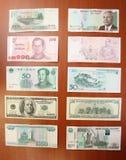 Kambodjansk riel vid fem tusentals (5000), thailändsk baht vid hundra (100), kinesiska yuans vid femtio (50), Förenta staterna do Royaltyfria Bilder