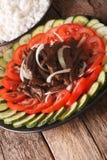 Kambodjanskt nötkött Lok Lak med närbild för nya grönsaker vertikalt royaltyfri foto