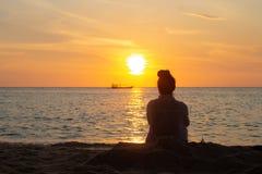 Kambodschanische Asiatin, die den Sonnenuntergang u. das Boot durch den Ozean aufpasst stockbilder