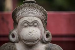 Kambodschanischer Affe, der Fabelwesengraue Steinskulptur mit zwei Ohrschleifen schaut Lizenzfreie Stockbilder