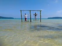 Kambodschanischer asiatischer Mann u. Frau, die auf Schwingen im Ozean stehen lizenzfreie stockfotos