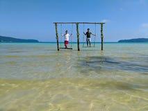 Kambodschanischer asiatischer Mann u. Frau, die auf Schwingen im Ozean stehen stockfotos