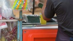 Kambodschanischer Mann, der an Kundenzuckerzuckerrohrsaft verkauft stock footage