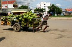 Kambodschanischer Verkäufer verschiebt Kokosnusswagen Lizenzfreie Stockfotografie