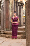 Kambodschanisches Mädchen im Khmer-Kleid, das in Bayon-Tempel in Angkor-Stadt steht Stockbilder