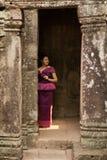 Kambodschanisches Mädchen im Khmer-Kleid, das in Bayon-Tempel in Angkor-Stadt steht stockfotos