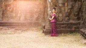 Kambodschanisches Mädchen im Khmer-Kleid, das an der Terrasse der Elefanten in Angkor-Stadt steht Lizenzfreie Stockfotografie