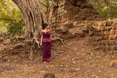 Kambodschanisches Mädchen im Khmer-Kleid durch eine alte Wand und Baum in Angkor Thom, Angkor-Stadt Lizenzfreie Stockbilder