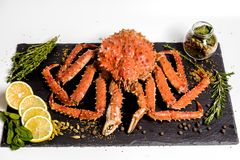 Kamchatka-Krabbe liegt auf einem Teller mit Gewürzen Stockfotografie