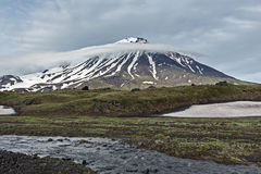 Kamchatka landskap: bergliten vik och OvalZimina vulkan Arkivfoton