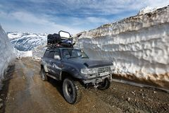 Off-road expedition car Toyota Land Cruiser driving on mountain road in snow tunnel surrounded by high snowdrifts stock photography