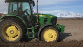 Modern tractor ploughing rough land on farming field. Farm work on sunny day. Kamchatka Peninsula, Russia - 29 May, 2018: Modern tractor John Deere PowerTech stock video footage