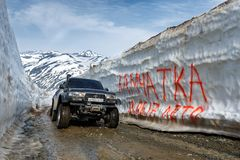 Off-road expedition car Toyota Land Cruiser driving on mountain road in snow tunnel. KAMCHATKA PENINSULA, RUSSIAN FAR EAST - JUNE 18, 2017: Japanese extreme off stock image