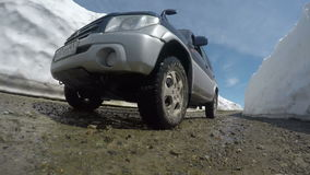 Off-road automobile Mitsubishi Pajero iO driving on mountain road in snow tunnel surrounded by high snowdrifts. KAMCHATKA PENINSULA, RUSSIAN FAR EAST - JUNE 18 stock video footage