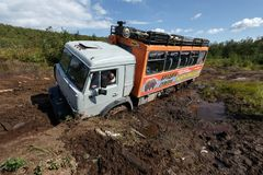 Russian off-road expedition truck KamAZ stuck 6-wheel drive in deep muddy forest road. KAMCHATKA PENINSULA, RUSSIAN FAR EAST - SEP 5, 2013: Russian off-road Royalty Free Stock Photo