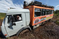 Russian off-road expedition truck KamAZ six-wheel drive stuck in deep muddy forest road Stock Photos