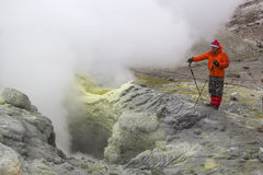KAMCHATKA, RUSSIA - JULY, 18. A tourist observes an active fumarole, producing volcanic gas. July 18, 2015 in Kamchatka, Russia. Stock Photo