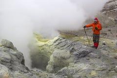KAMCHATKA RYSSLAND - JULI, 18 En turist observerar en aktiv fumarole och att producera vulkanisk gas Juli 18, 2015 i Kamchatka, R Arkivfoto