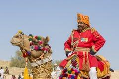 Kameel en de Indische mensen die traditionele Rajasthani-kleding de dragen nemen aan M. deel Woestijnwedstrijd als deel van Woest Stock Foto's