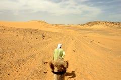Kameel en zijn bestuurder in de woestijn Stock Foto