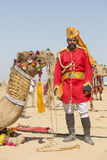 Kamel- och indiermän som bär den traditionella Rajasthani klänningen, deltar i herr Desertera striden som delen av ökenfestivalen Arkivbild
