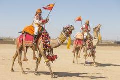 Kamel- och indiermän som bär den traditionella Rajasthani klänningen, deltar i herr Desertera striden som delen av ökenfestivalen Royaltyfri Foto