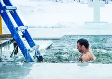 Kamenetz-Podolsk ucrânia 19 de janeiro 2017 O homem banha-se em um furo do gelo Festa do esmagamento Imagens de Stock