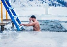 Kamenetz-Podolsk ucrânia 19 de janeiro 2017 O homem banha-se em um furo do gelo Festa do esmagamento fotografia de stock royalty free