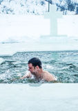 Kamenetz-Podolsk. UKRAINE. January 19. 2017. The man bathes in an ice hole. Feast of the Epiphany. Royalty Free Stock Photos
