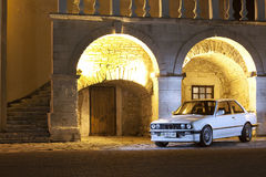 Kamenetz-Podolskiy, Ukraine - April 13, 2012. BMW 325 E 30, whit. E car in the old town, classic car, lowrider, lowride car in the lights of the night city Royalty Free Stock Images